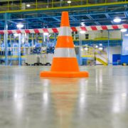 Orange safety cone onSydney warehouse floor- flooring systems
