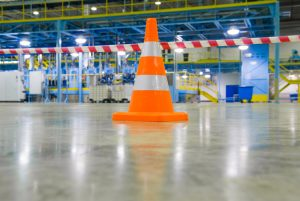 Orange safety cone onSydney warehouse floor- flooring systems